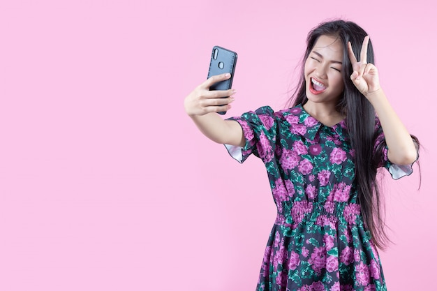 Teenage girl showing phone and facial emotions Free Photo