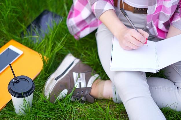 10代の少女学生が公園でノートに書きます。大学での試験準備 Premium写真