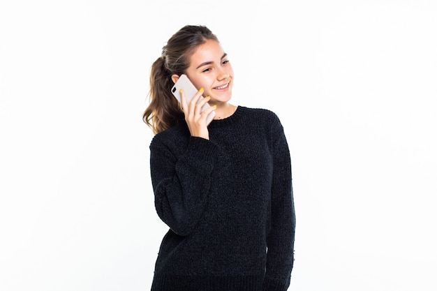 Adolescente che parla su un telefono cellulare isolato sulla parete bianca Foto Gratuite