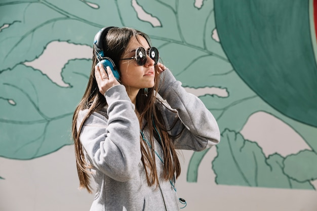 Teenage girl wearing headphones and sunglasses in front of painted wall Free Photo