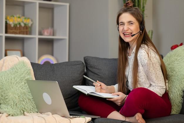 ベッドの上に座ってラップトップを使用してヘッドフォンを着ている10代の少女。自宅のウェブカメラで友人と通信するオンライン遠隔学習のためにコンピューターで呼び出す幸せな10代の学生会議 Premium写真