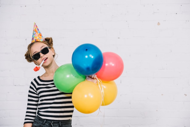 Teenage girl wearing sunglasses holding party horn in her mouth and catching colorful balloons in hand Free Photo
