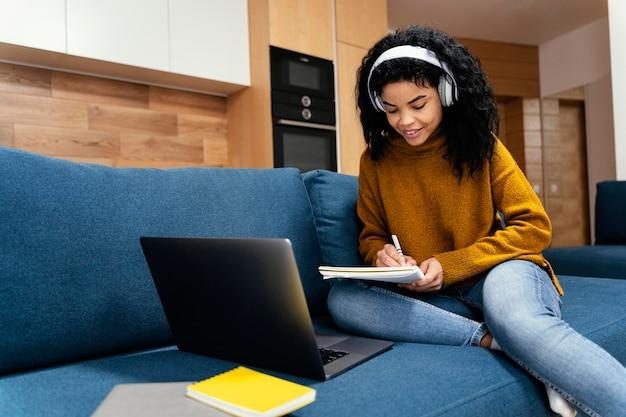 オンライン学校の間にラップトップとヘッドフォンを持つ10代の少女 無料写真
