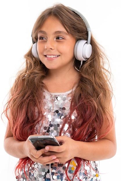 Девочка-подросток с длинными светлыми волосами, окрашенными в розовые кончики, в блестящем легком платье, стоя с наушниками и держа телефон в руке Premium Фотографии