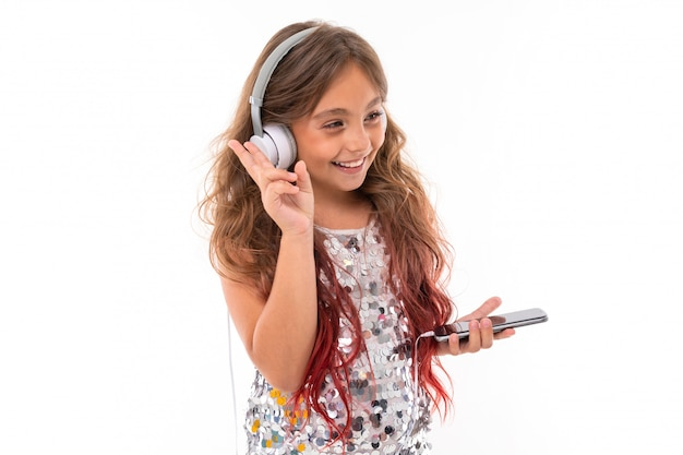 Teenage girl with long blonde hair dyed with tips pink, in shiny light dress, standing with headphones and holding phone in hand Premium Photo