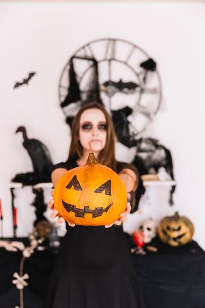 Teenage girl with vampire makeup holding pumpkin ahead Free Photo