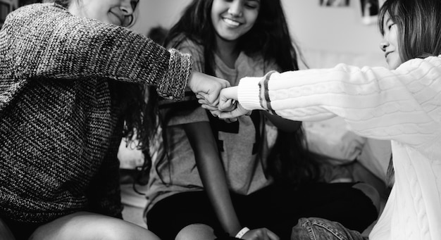 Teenage girls in a bedroom fist bumping friendship concept Free Photo