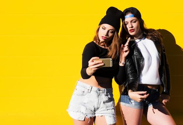 Teenage girls friends outdoors make selfie on a phone. Premium Photo