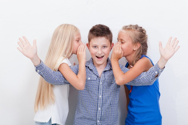 Adolescenti che bisbigliano nelle orecchie di un ragazzo teenager segreto sulla parete bianca Foto Gratuite