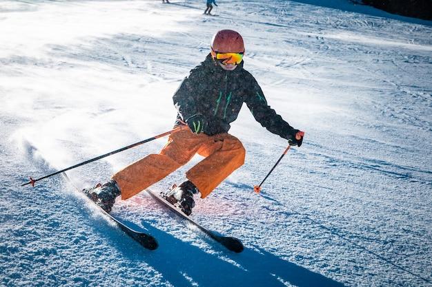 晴れた日の間に斜面を回す10代の男性スキーヤー Premium写真