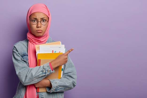 Teenage muslim girl student poses with papers and textbooks, points aside on free space, wears round optical glasses and pink hijab Free Photo