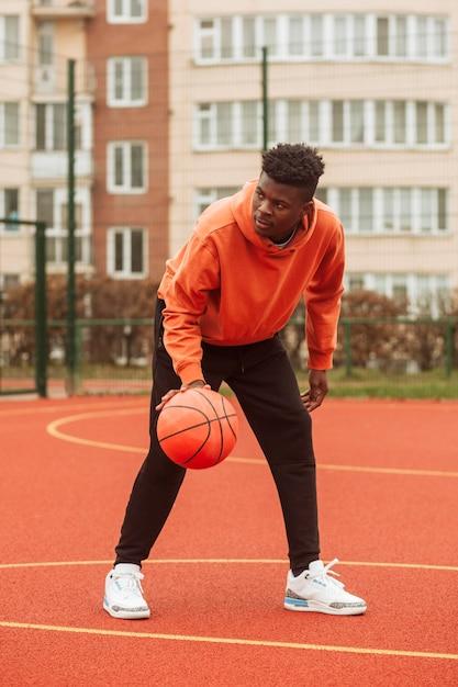 Подросток играет в баскетбол на открытом воздухе Бесплатные Фотографии
