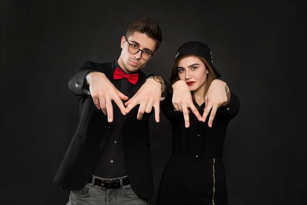 Подростковая улыбающаяся рэп-пара в черной одежде и черной кепке. изолированные на черном фоне. Premium Фотографии
