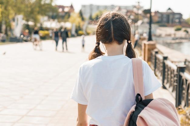 バックパックで通りを歩いて10代の学生の女の子 Premium写真