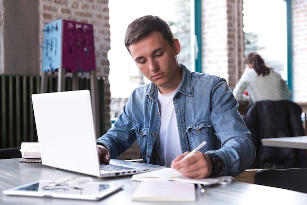 Teenage student sitting at table with notebook and writing Free Photo