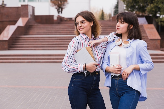 Teenage students in light shirts standing with books Free Photo