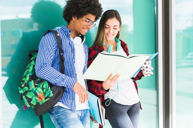 Teenage students with books and their bags standing against glass looking at book Free Photo