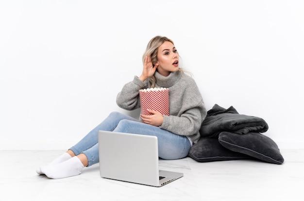 Блондинка подросток ест попкорн во время просмотра фильма на ноутбуке, слушая что-то, положив руку на ухо Premium Фотографии