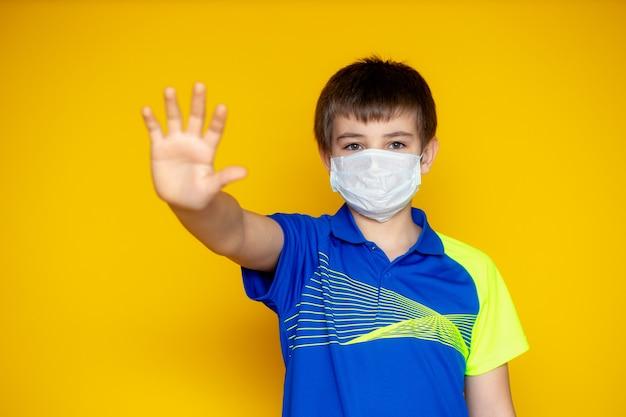 黄色の壁に11〜12歳の少年。ティーンエイジャーは、コロナウイルスとインフルエンザの発生中に顔のマスクを着用しています。ウイルスや病気に対する保護。 Premium写真