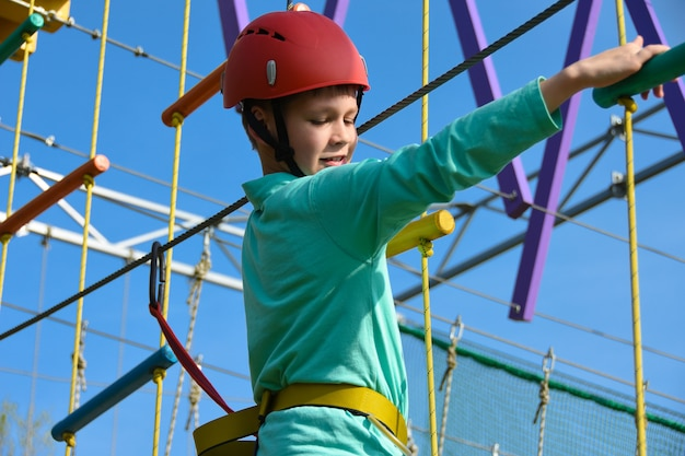 Teenager boy moves the vertical grid on the obstacle course in the amusement park Premium Photo