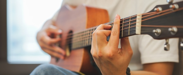 Teenager boy open laptop for search song and playing classical guitar Premium Photo