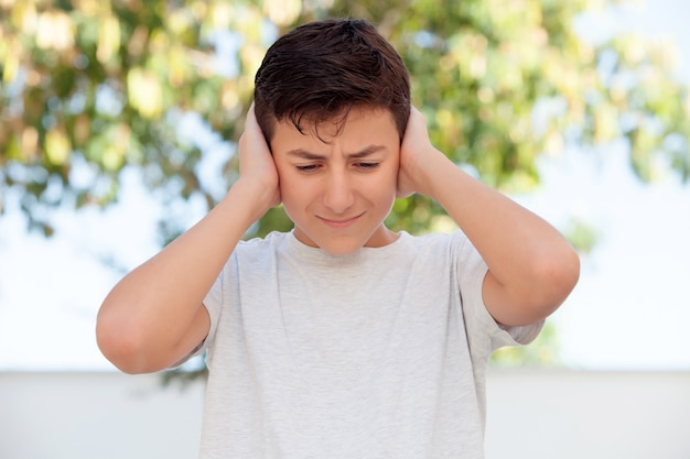 Teenager boy outdoor covering his ears Premium Photo