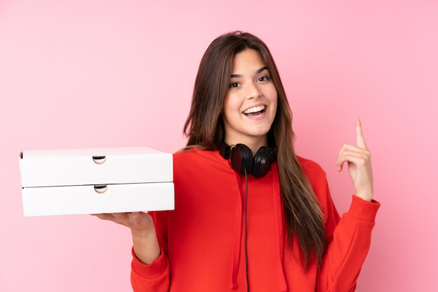 Teenager brazilian girl holding pizza boxes over isolated pink wall pointing up a great idea Premium Photo