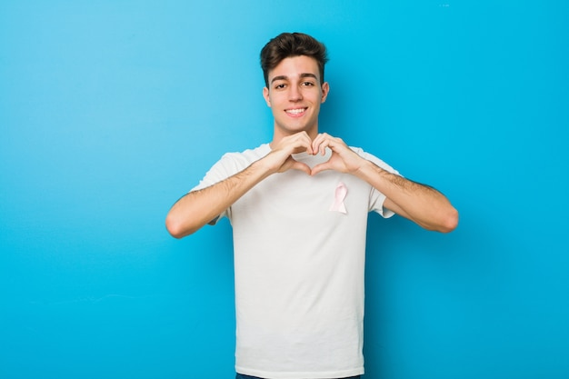 Teenager caucasian man with a pink bow.  of fight against cancer. Premium Photo