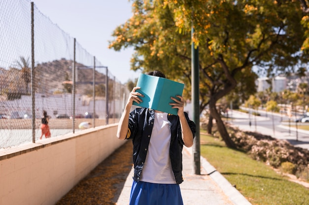 Teenager closing face by book Free Photo