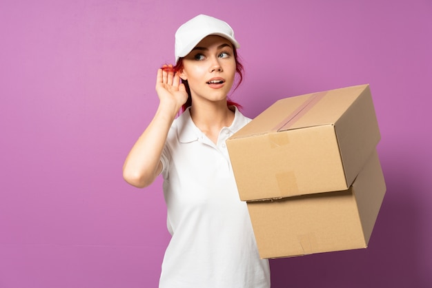 Девочка доставки подростка, изолированные на фиолетовый, слушая что-то, положив руку на ухо Premium Фотографии