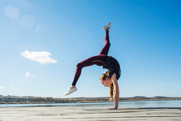Teenager doing gymnastic on pier Free Photo