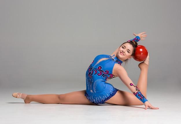 Подросток делает гимнастические упражнения с красным гимнастическим мячом Бесплатные Фотографии