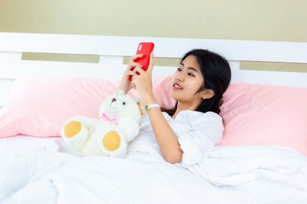 Teenager female use smartphone on the bed Free Photo
