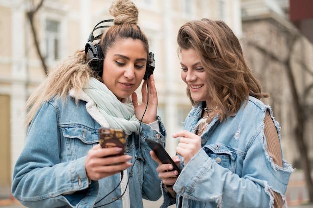 Amici adolescenti che condividono canzoni all'aperto Foto Gratuite