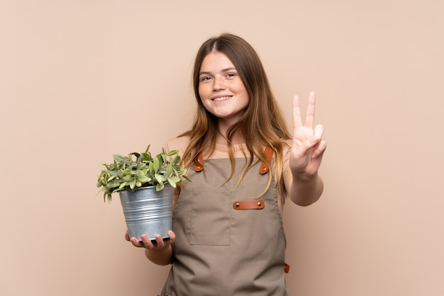 Teenager gardener girl holding a plant smiling and showing victory sign Premium Photo