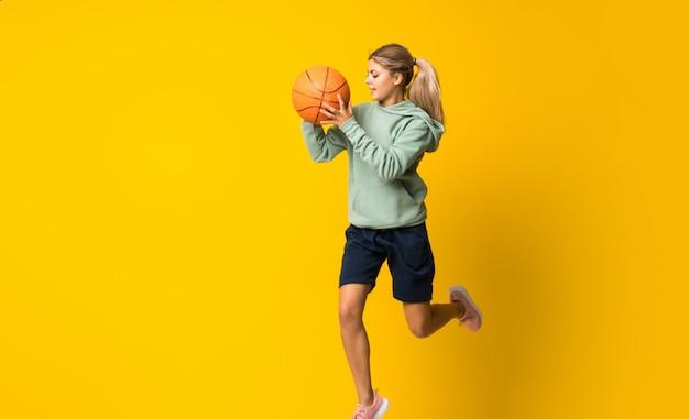 Teenager girl basketball ball jumping over isolated yellow wall Premium Photo