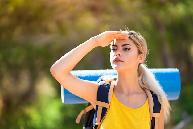 Teenager girl hiking at outdoors looking far away with hand to look something Premium Photo