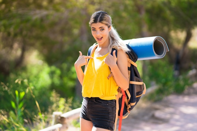 Teenager girl hiking at outdoors with surprise facial expression Premium Photo