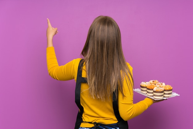 Teenager girl holding lots of different mini cakes over isolated purple wall pointing back with the index finger Premium Photo