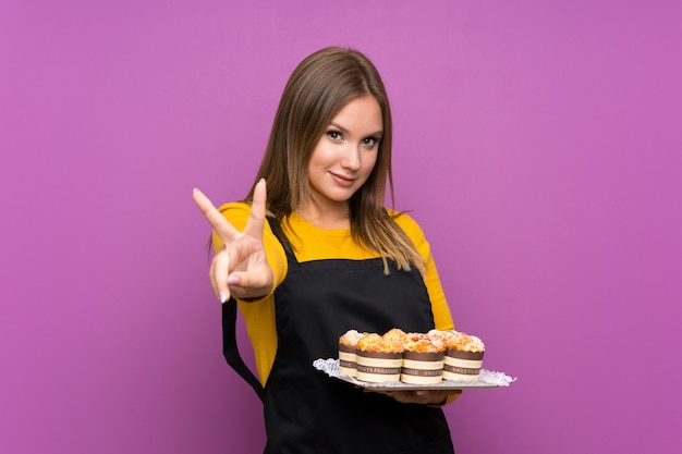 Teenager girl holding lots of different mini cakes over isolated purple wall smiling and showing victory sign Premium Photo