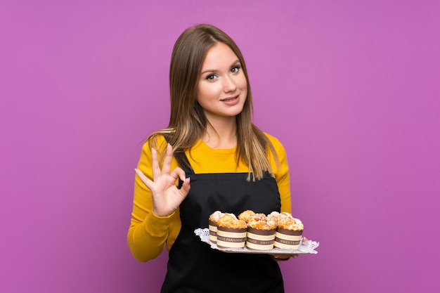 Teenager girl holding lots of different mini cakes purple showing an ok sign with fingers Premium Photo