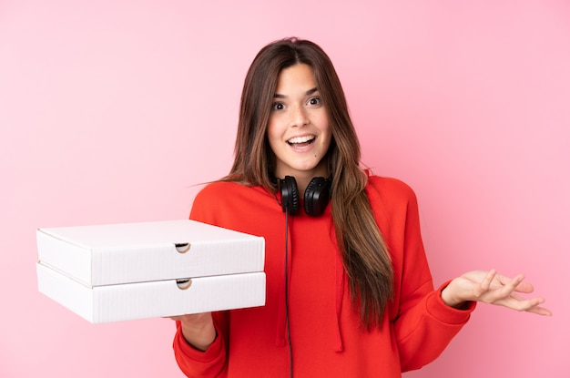 Teenager girl holding pizzas boxes over isolated wall Premium Photo