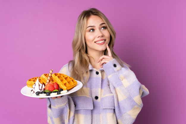 Teenager girl holding waffles on purple wall thinking an idea while looking up Premium Photo
