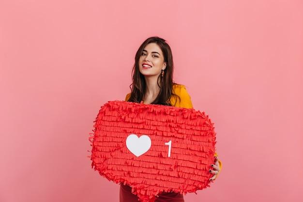 Девушка-подросток в ярком наряде улыбается, держа на розовой стене красный знак «нравится» из instagram. Бесплатные Фотографии