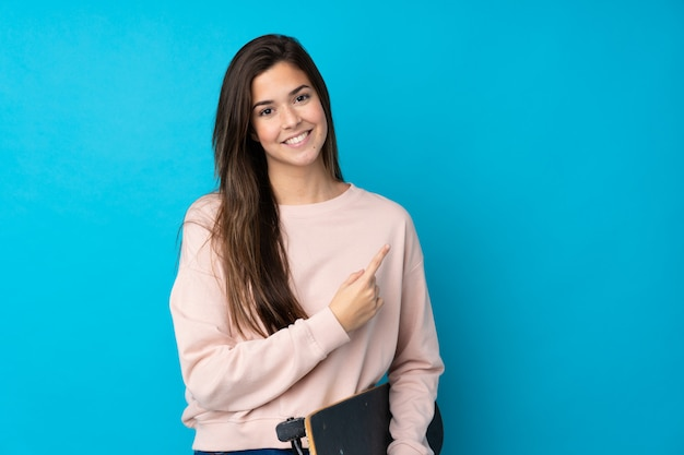 Teenager girl over isolated blue wall with a skate and pointing to the side Premium Photo