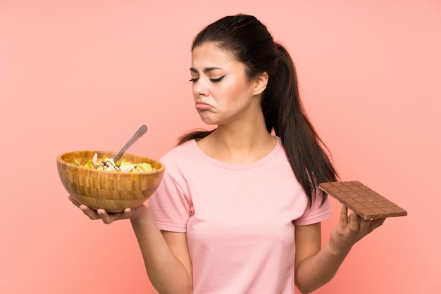 Teenager girl  over isolated pink wall with salad and chocolat and having doubts Premium Photo