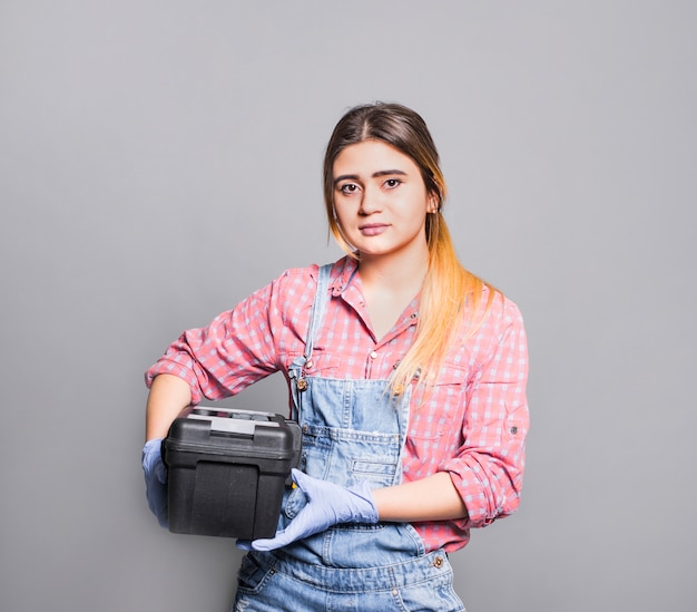 Teenager girl in overall with tool box Free Photo