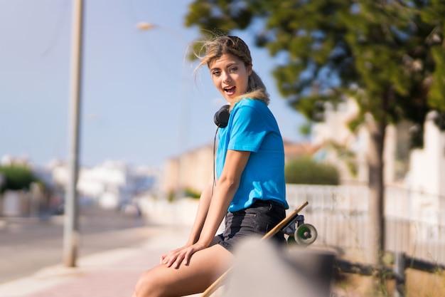 驚きの表情で屋外でスケートを持つティーンエイジャーの女の子 Premium写真