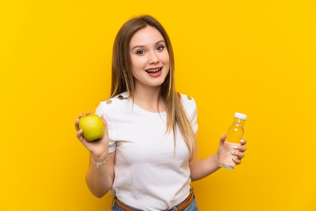 Teenager girl over yellow wall with an apple and a bottle of water Premium Photo