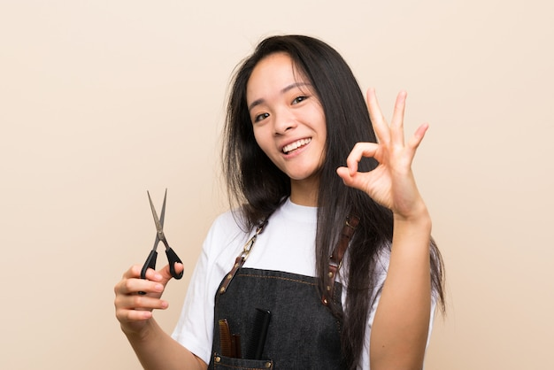 Teenager hairdresser girl showing ok sign with fingers Premium Photo